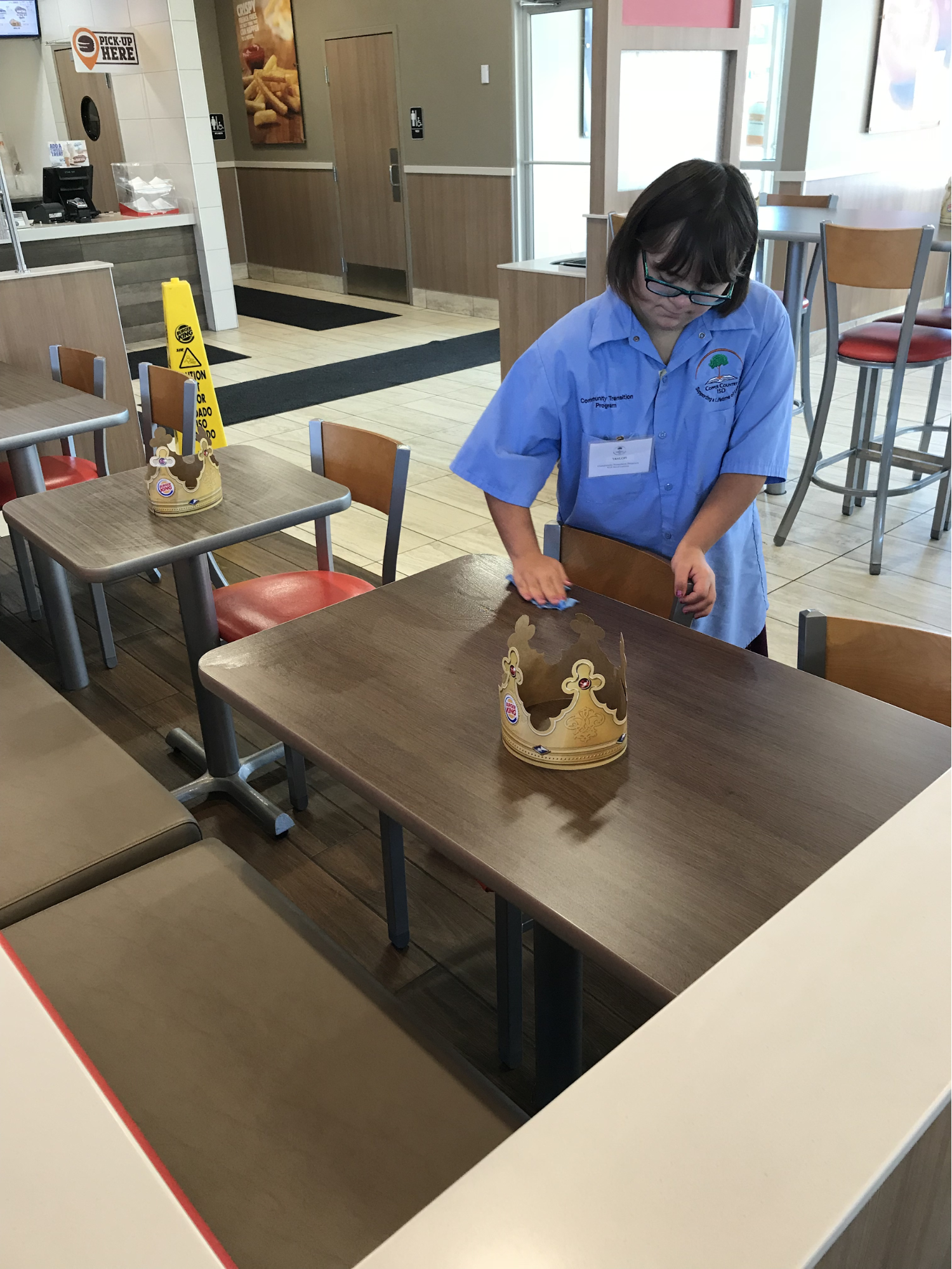 Student helping the local Burger King by cleaning tables