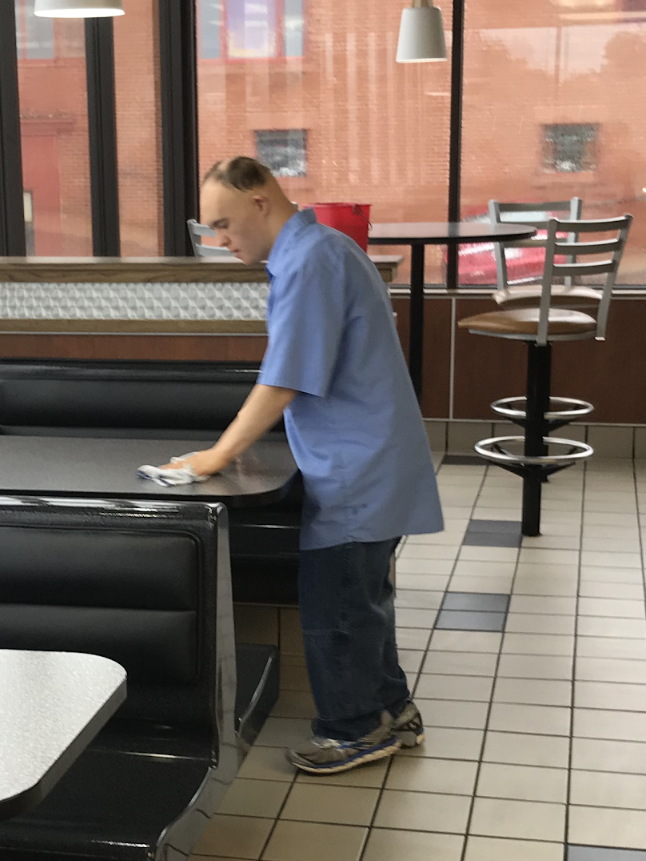 Student working, cleaning tables at a local restaurant