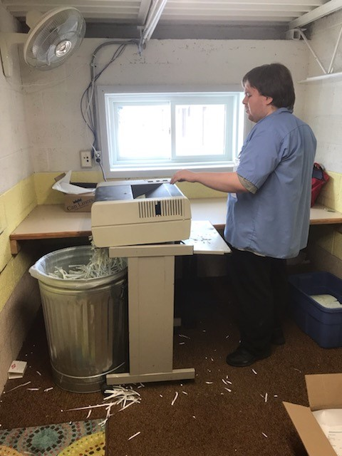 Student helping a local business by shredding unneeded documents